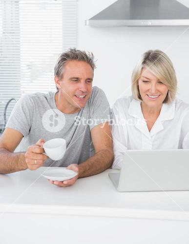 Content couple using laptop in the morning