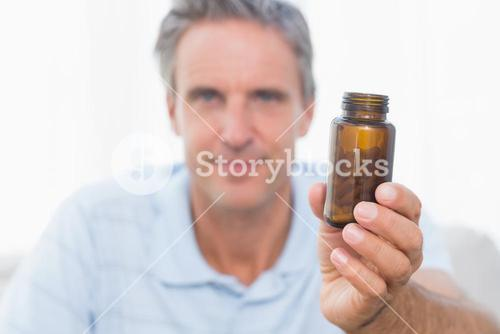 Man showing bottle of pills to camera