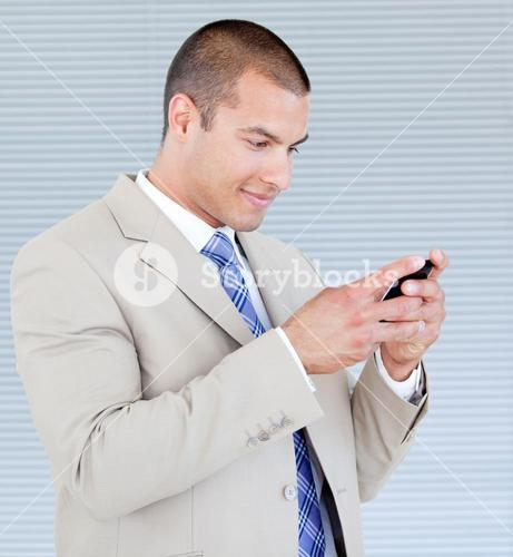 Attractive businessman sending a text