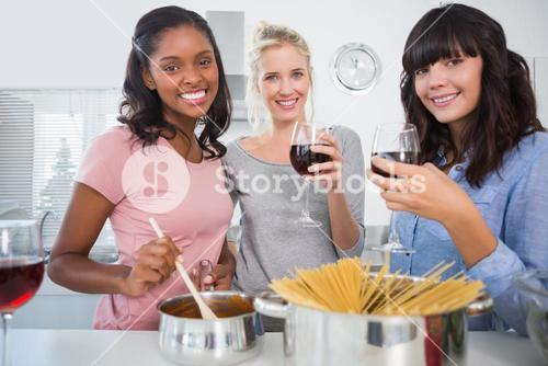 Cheerful friends making spaghetti dinner together and drinking red wine