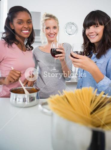 Happy friends making spaghetti dinner together and drinking red wine