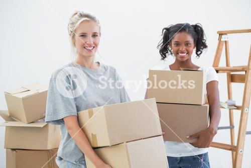 Cheerful housemates carrying moving boxes