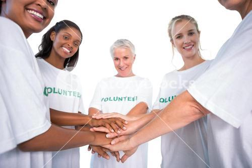 Group of female volunteers with hands together smiling at camera