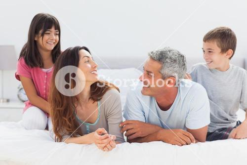 Smiling family talking together on bed