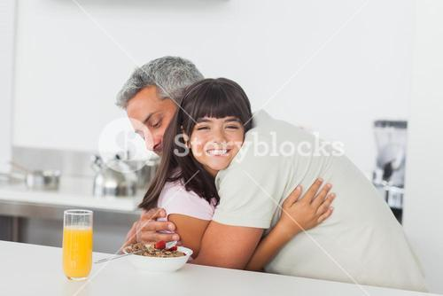 Little girl gives a hug to her father