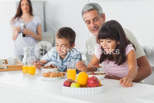 Cute family eating breakfast in kitchen together