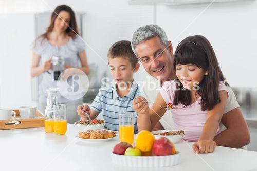 Happy family eating breakfast in kitchen together