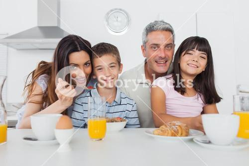 Cheerful family eating breakfast together