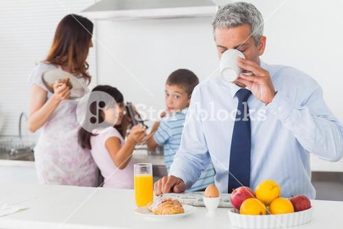 Father drinking coffee while his family are cooking