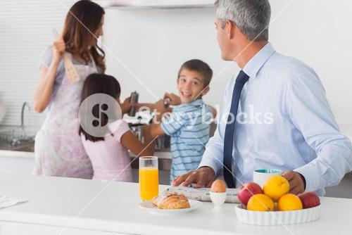 Father looking at his family cooking in the kitchen