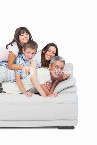 Children lying on their parents on sofa
