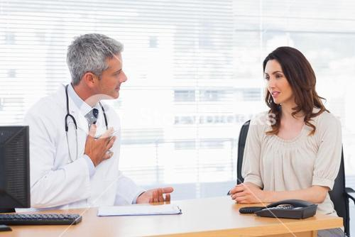 Serious patient talking with her doctor about illness