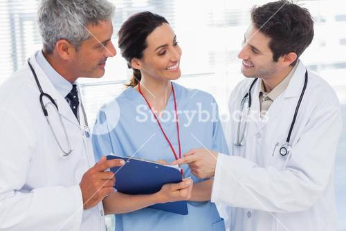 Smiling nurse and doctors looking together a file