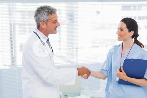 Smiling doctor shaking hands with nurse