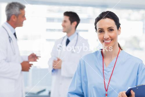 Nurse smiling at camera while doctors are talking together