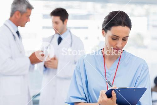 Nurse writing on a clipboard while doctors are talking together