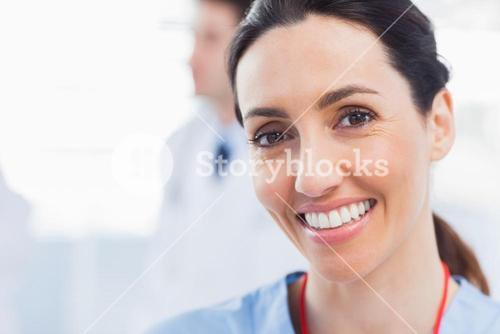 Smiling nurse looking at camera with a doctor behind her