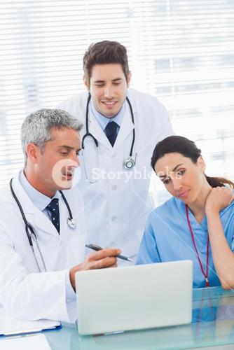 Nurse and doctors working together on laptop