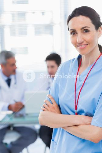 Nurse crossing arms with her colleagues behind