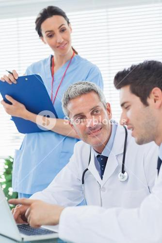 Nurse listening to doctors talking about something on their laptop