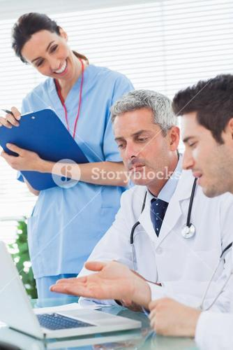 Smiling nurse listening to doctors talking about something on their laptop