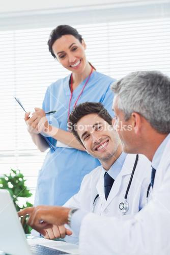 Happy nurse listening to doctors talking about something on their laptop