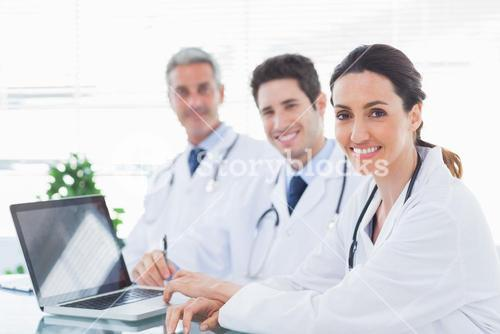 Doctors with laptop smiling at camera