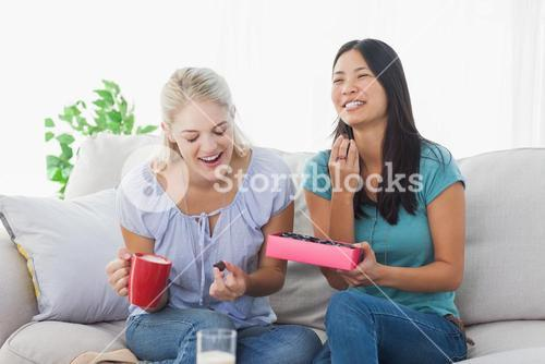 Friends sharing a box of chocolates and laughing