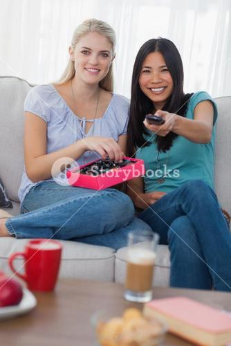 Friends sharing a box of chocolates and watching tv