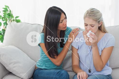 Concerned woman comforting her crying friend