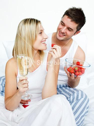 Lovers celebrating an engagement with strawberries and champagne