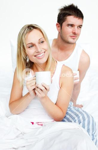Couple drinking a cup of tea in bed