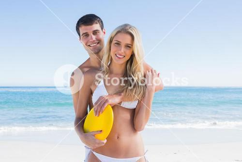 Man holding frisbee and hugging his girlfriend