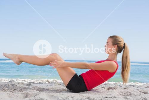 Fit blonde doing pilates core exercise