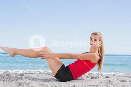 Fit blonde doing pilates core exercise smiling at camera