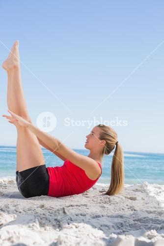 Athletic blonde doing pilates core exercise