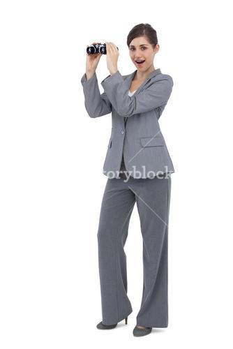 Astonished businesswoman posing with binoculars