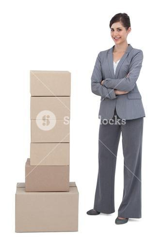 Smiling businesswoman posing with cardboard boxes