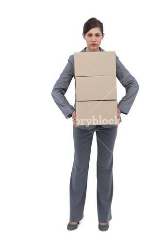Serious businesswoman carrying cardboard boxes