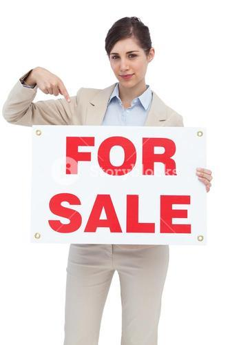 Estate agent holding and pointing to for sale sign