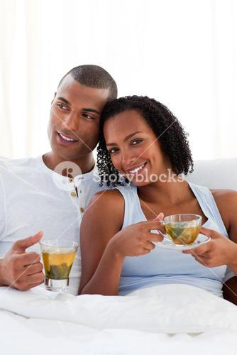 Intimate couple drinking a cup of tea on their bed