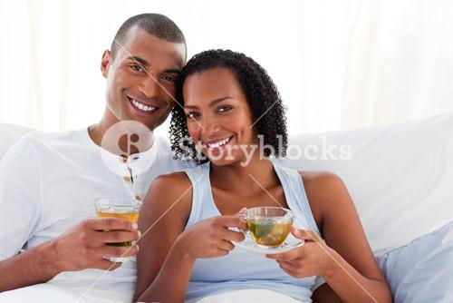 Smiling couple drinking a cup of tea on their bed