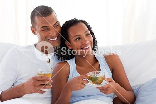 Jolly couple drinking a cup of tea on their bed