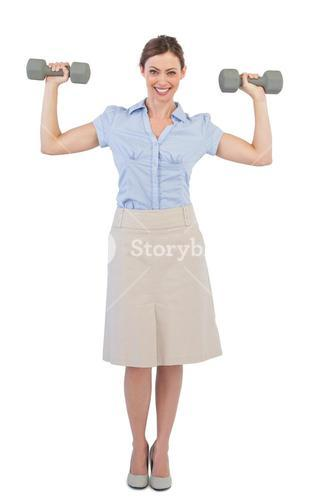 Strong businesswoman posing with dumbbells