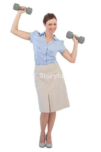 Strong businesswoman lifting dumbbells looking at camera