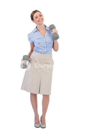 Happy businesswoman lifting dumbbells looking