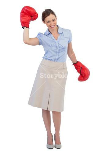 Happy businesswoman posing with red boxing gloves