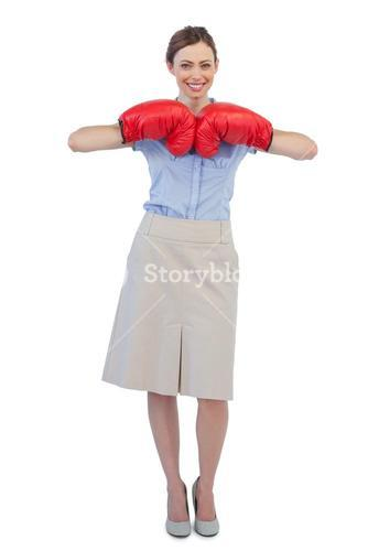 Cheerful businesswoman posing with red boxing gloves