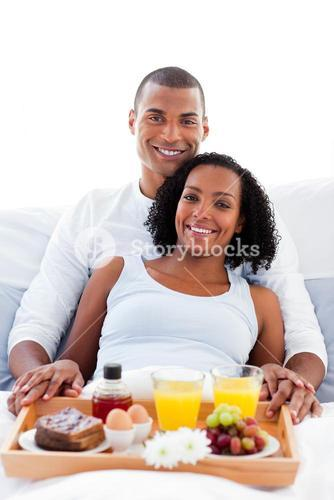 Couple having breakfast lying on their bed
