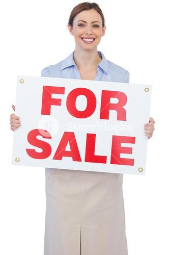 Cheerful estate agent posing with for sale sign